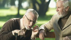 Oude gepensioneerde die met hoorzittingsprobleem aan vriend luisteren, die op parkbank zitten stock video