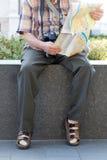 Oude gepensioneerde die in sokken en sandals bestemming op kaart zoekt stock fotografie