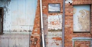 Oude gereduceerde die muur van bakstenen en golfijzer wordt gemaakt stock afbeelding