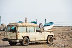 Oude geroeste 4x4 op een strand in Oman stock afbeelding