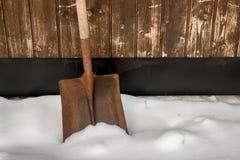 Oude geroeste schop in de sneeuw buiten een garagedeur royalty-vrije stock afbeeldingen