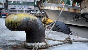 Oude geroeste vastleggende meerpaal met geknoopte zeevaartkabels Ulleungdo, Zuid-Korea Pijlinktvis vissersboot bij de Haven die v stock footage
