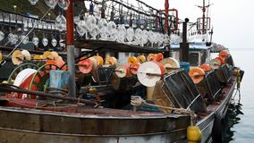 Oude geroeste vastleggende meerpaal met geknoopte zeevaartkabels Ulleungdo, Zuid-Korea Pijlinktvis vissersboot bij de Haven die v stock videobeelden