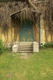 Oude geruïneerde portiek door een baksteenhuis en een oude klimop stock foto's