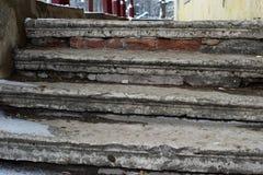 Oude geruïneerde steentrap met huisvuil in de winter stock afbeelding