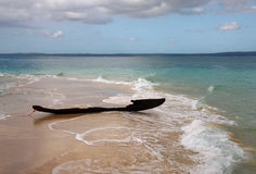 Oude geruïneerde vissersboot bij zandige bank stock foto's