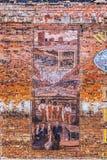 Oude geschilderde beelden bij de baksteen Stock Foto's