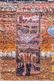Oude geschilderde beelden bij de baksteen Stock Afbeelding