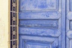 Oude geschilderde blauwe deur van doorstane hout en keramische tegels op een oude pleistermuur in Spanje stock foto's