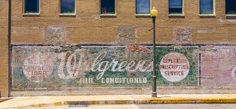 Oude geschilderde reclame bij de muur Stock Foto's