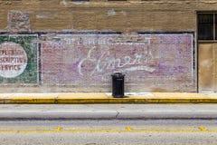 Oude geschilderde reclame bij de muur Stock Afbeeldingen