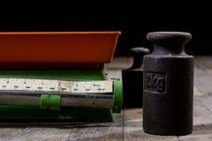 Oude gewicht en gewichten op een houten lijst Oude gebruikte keukenschaal Royalty-vrije Stock Afbeelding
