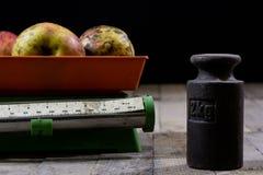 Oude gewicht en gewichten op een houten lijst Oude gebruikte keukenschaal Stock Afbeeldingen