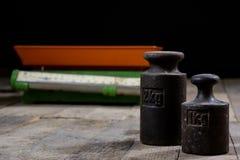Oude gewicht en gewichten op een houten lijst Oude gebruikte keukenschaal Royalty-vrije Stock Fotografie
