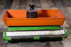 Oude gewicht en gewichten op een houten lijst Oude gebruikte keukenschaal Stock Foto