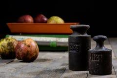 Oude gewicht en gewichten op een houten lijst Oude gebruikte keukenschaal Stock Fotografie