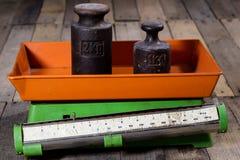 Oude gewicht en gewichten op een houten lijst Oude gebruikte keukenschaal Royalty-vrije Stock Foto