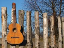 Oude gitaar op de omheining Stock Foto's