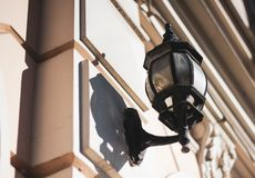 Oude glaslantaarn in een zwart verdraaid kader op de witte muur van het stadsgebouw Muurlamp op een Zonnige dag stock foto's
