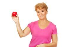 Oude glimlachende vrouw die rood stuk speelgoed hart houdt Royalty-vrije Stock Fotografie