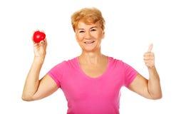 Oude glimlachende vrouw die rood stuk speelgoed hart met omhoog duim houden Stock Afbeelding