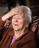 Oude grijs-haired vrouw die aan hoofdpijn lijden royalty-vrije stock fotografie