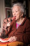 Oude grijs-haired vrouw die plak van watermeloen eten stock foto