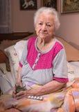 Oude grijs-haired zieke vrouw Stock Foto