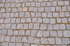 Oude grijze bestrating in een patroon in een oude middeleeuwse Europese stad Stock Foto's