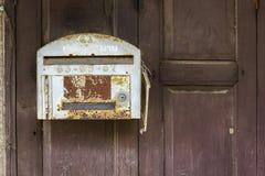 Oude grijze brievenbus op bruine houten muur stock foto's