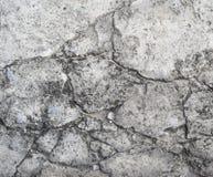 Oude grijze cementmuur met barsten Stock Afbeeldingen