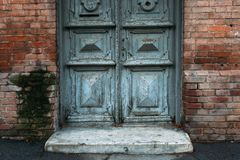 Oude grijze deur met patronen Bakstenen muur royalty-vrije stock afbeeldingen