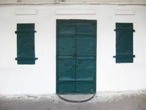 Oude groene deuren en kleine vensters Stock Afbeeldingen