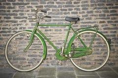 Oude groene die fiets tegen een bakstenen muur wordt geparkeerd stock afbeeldingen