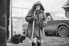 Oude grootmoeder dichtbij zijn huis in Rusland Stock Afbeelding