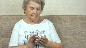 Oude grootmoeder die een slimme telefoon thuis houden stock videobeelden