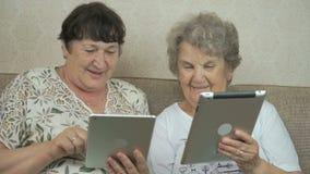 Oude grootmoeders die zilveren digitale tabletten houden stock footage