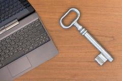 Oude grote sleutel en laptop Stock Foto's