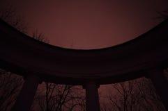 Oude halfronde colonnade in mystiek park in rood licht Stock Fotografie
