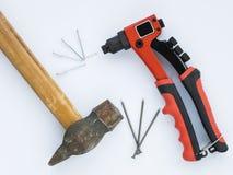 Oude hamer en spijkers tegen nieuwe Klinknagelkanon en Klinknagels Stock Afbeelding