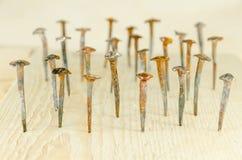 Oude hand-gesmede die spijkers in een raad worden gehamerd stock afbeelding