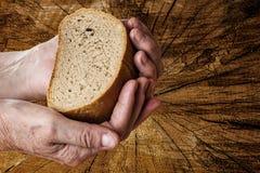 Oude handen die brood houden stock foto