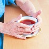 Oude handen die een kop thee houden stock afbeeldingen