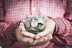 Oude handen die muntstukken houden Stock Foto's