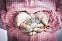 Oude handen die muntstukken houden Royalty-vrije Stock Foto's