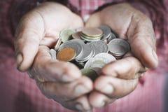 Oude handen die muntstukken houden Stock Foto
