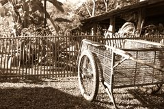 Oude handkar op gazon voor oude bamboeomheining en loods Stock Afbeeldingen