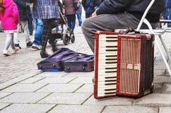Oude harmonika slechte musicus bij voorbijgangers van mensenachtergrond royalty-vrije stock afbeeldingen