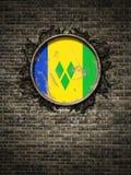 Oude Heilige Vincent en de Grenadinesvlag in bakstenen muur Stock Foto