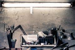 Oude het werkhulpmiddelen, plank op een muur over een oude uitstekende werkbank in een huisgarage stock foto's